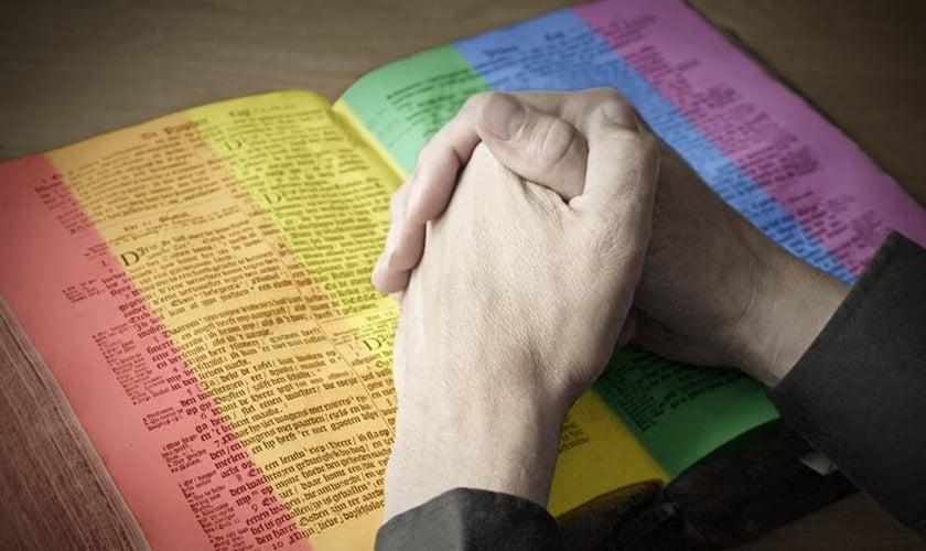 Imagem ilustrativa: Edição mostra homem repousando as mãos sobre Bíblia com páginas coloridas. (Imagem: Salon)