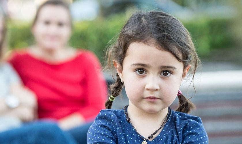 Imagem ilustrativa de criança com lésbicas ao fundo. (Foto: Considering Adoption)