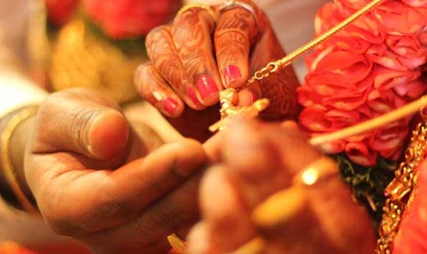 Casal hindu segura pingente nas mãos. (Foto: Marriage.com)