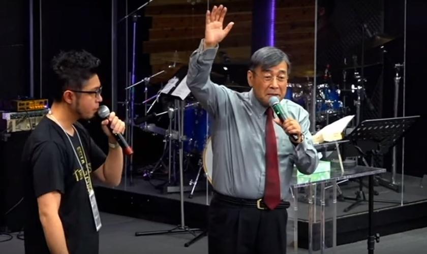 Pastor Hiraoka Shuuji (direta) alerta para a urgência de um movimento missionário no Japão. (Foto: YouTube/Reprodução)