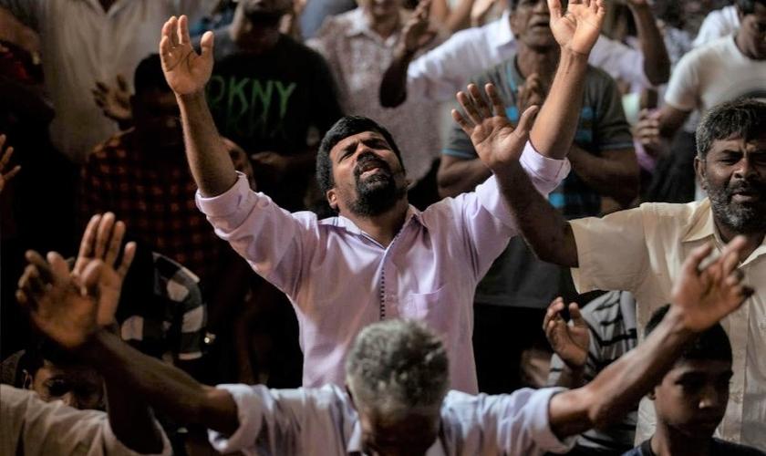 Membros da Igreja de Sião, que foi bombardeada no domingo de Páscoa, oram em um salão comunitário em Batticaloa, no Sri Lanka. (Foto: Reuters/Danish Siddiqui)