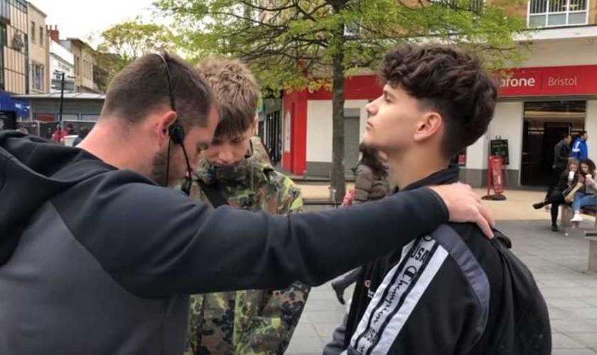 Evangelista Phillip Blair (esquerda) ora com os adolescentes Joe e Mathias, após pregar nas ruas de Bristol (Inglaterra) e fazer um apelo, perguntando quem gostaria de se entregar a Jesus. (Imagem: Youtube / Reprodução)