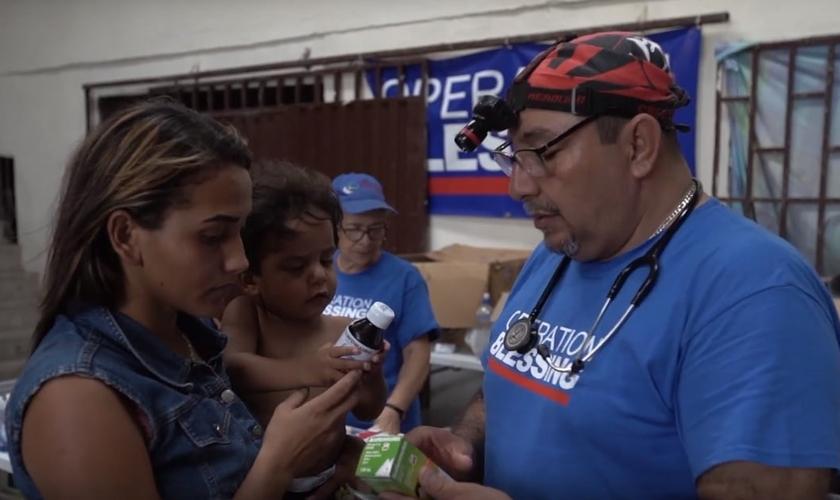 Missionário presta atendimento médico a Izana e seu filho Wilson. (Imagem: CBN News)