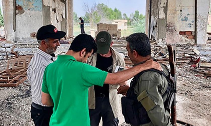 Dave Eubank (atrás) em momento de oração com sírios, em igreja destruída pela guerra. (Foto: Free Burma Rangers)