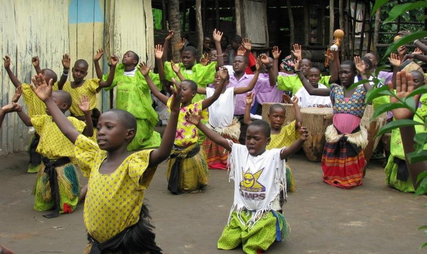 Crianças e adultos durante oração em comunidade de Uganda. (Foto: Set Free Ministries)