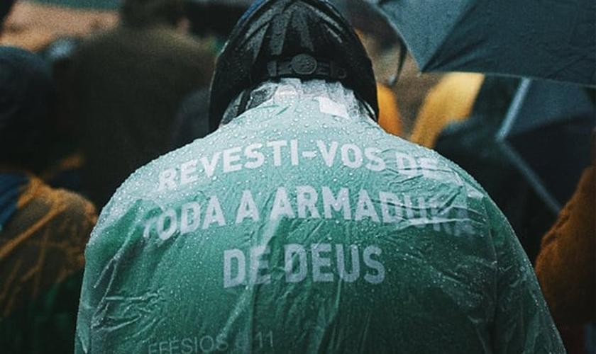 Em Porto Alegre, homem usa capa com versículo bíblico durante ato. (Foto: Matheus Bazzo)