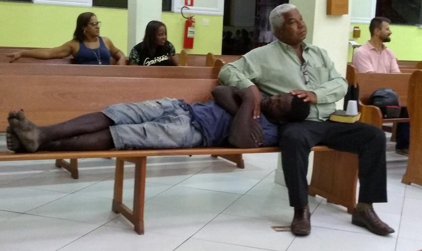 Após receber um copo de água e um abraço, o morador de rua sentiu-se à vontade para reclinar sua cabeça no colo do Sr. Orlando. (Foto: Facebook / Cleberson Santos)