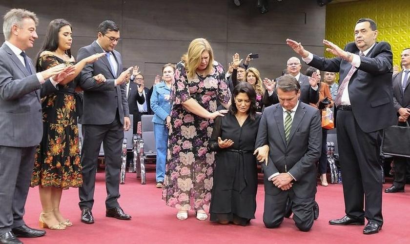 Jair Bolsonaro e sua esposa, Michelle, se ajoelham para que líderes orem pelo governo, durante culto da Assembleia de Deus, em Manaus. (Foto: BNC Amazonas)
