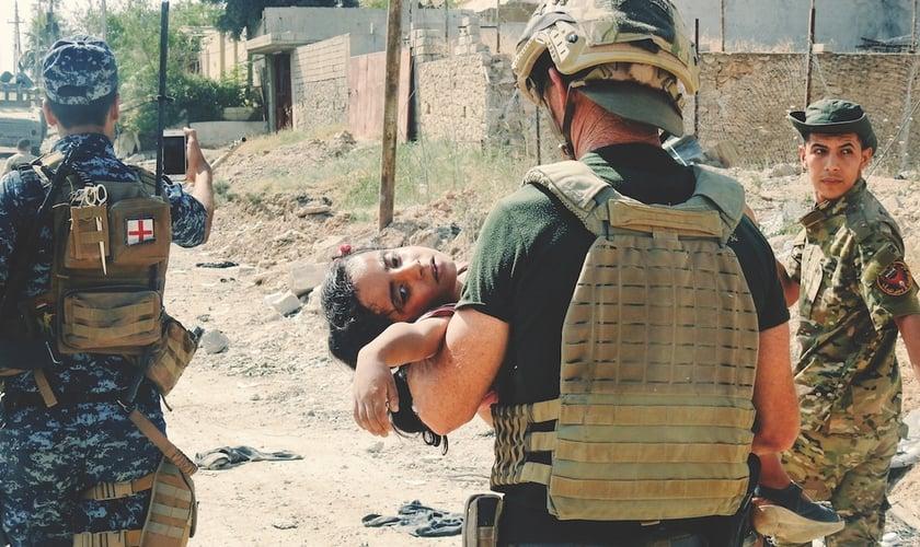 David Eubank carrega garota ferida em campo de guerra. (Foto: Fuller Studio)