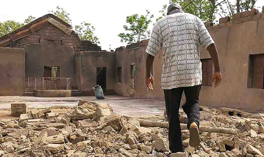 Cristão caminha por escombros de igreja incendiada na Nigéria. (Foto: Portas Abertas)