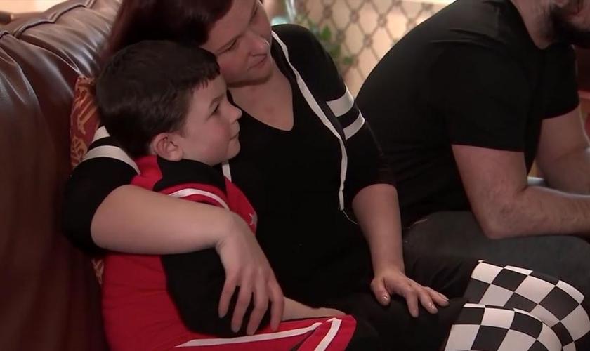 Noah Woods é abraçado pela mãe, após salvar sua família de um incêndio. (Foto: ABC News)