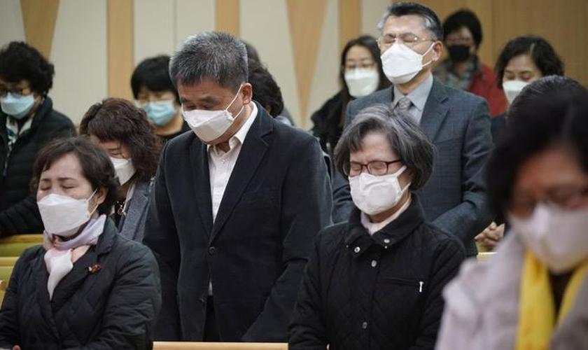 Fiéis participam de culto com máscaras para proteger a boca e o nariz e evitar contaminação. (Foto: Tempo.co.English)