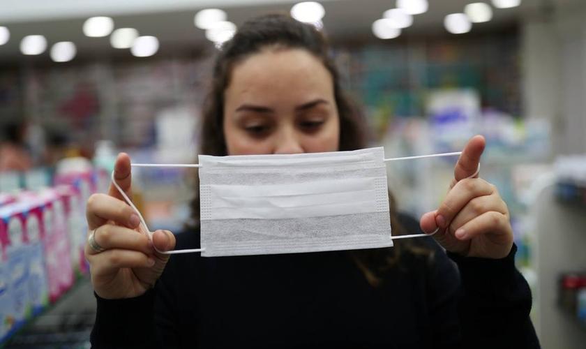 Vendedora mostra máscara de proteção, em Guarulhos (SP), usada diante da epidemia do novo coronavírus pelo mundo. (Foto: Amanda Perobelli/Reuters)