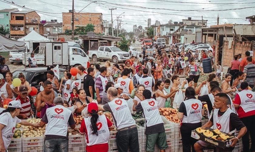 Voluntários distribuem alimentos para pessoas que perderam renda na periferia de São Paulo. (Foto: Unisocial)