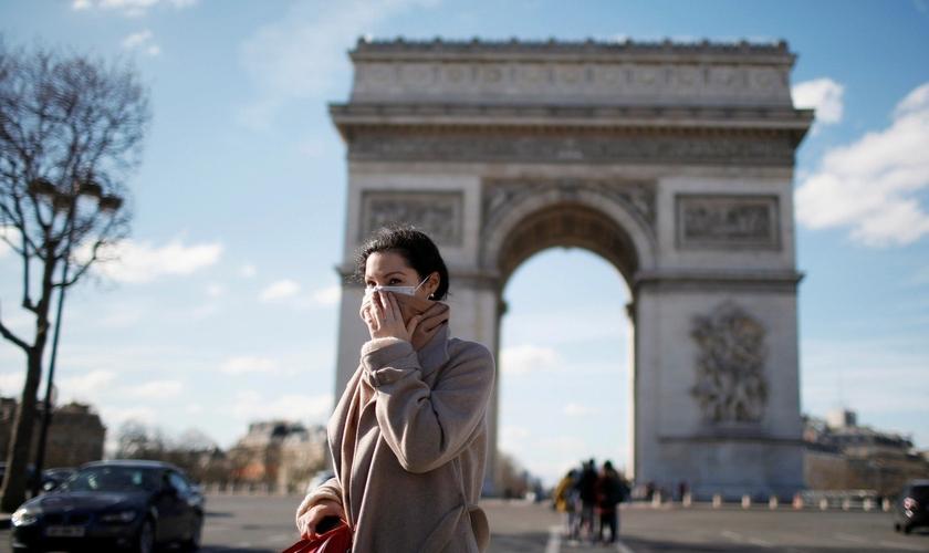 Mulher usa máscara de proteção perto do Arco do Triunfo, em Paris, na França. (Foto: Gonzalo Fuentes/Reuters)