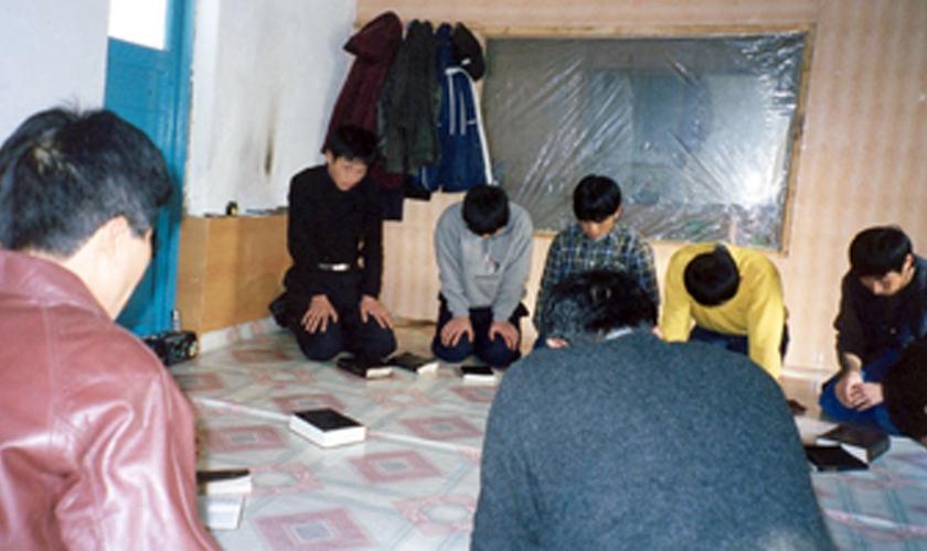 Cristãos oram ajoelhados em igreja clandestina da Coreia do Norte. (Foto: GodReports)