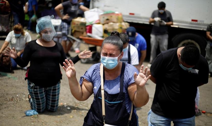 Fornecedores do maior centro de suprimentos de frutas e legumes de San Salvador em momento de oração. (Foto: EFE/Rodrigo Sura)