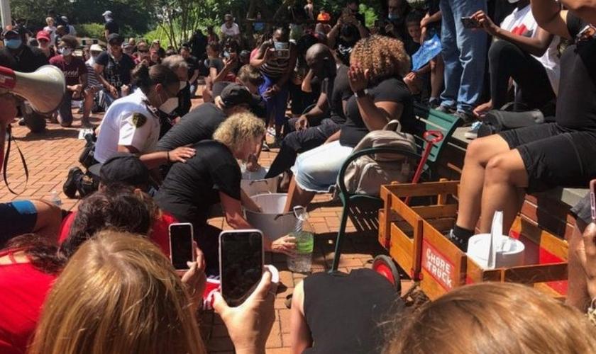Policiais se sentiram tocados ao ver os líderes cristãos promovendo o momento pacífico de lavar os pés de manifestantes negros, na Carolina do Norte. (Foto: The Sun)