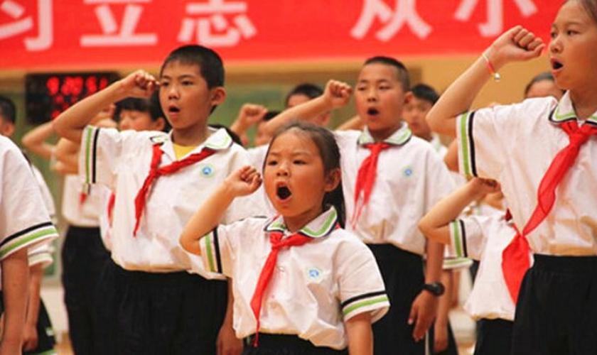 """'Jovens Pioneiros' em uma escola primária na região autônoma de Ningxia Hui fazem um juramento durante uma atividade do evento """"O Lenço Vermelho Segue a Festa"""" no Dia das Crianças. (Foto: Bitter Winter)"""