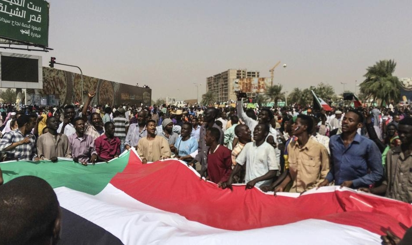 Sudaneses celebram a deposição do então presidente Omar al-Bashir em 2019, após 30 anos no poder. (Foto: Associated Press)