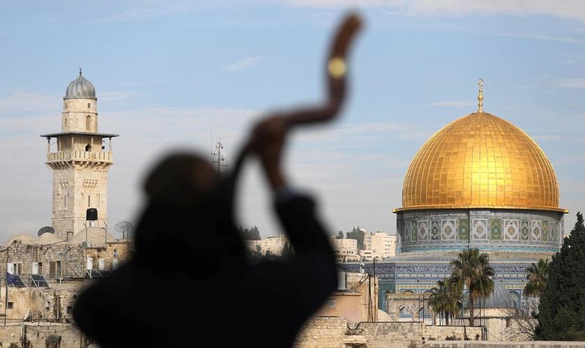 Homem toca shofar com o Monte do Templo ao fundo, em Jerusalém. (Foto: Reuters/Ammar Awad)