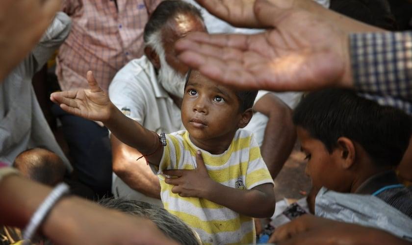 Criança estende a mão para receber comida em Nova Delhi, na Índia. (Foto: AP/Manish Swarup)