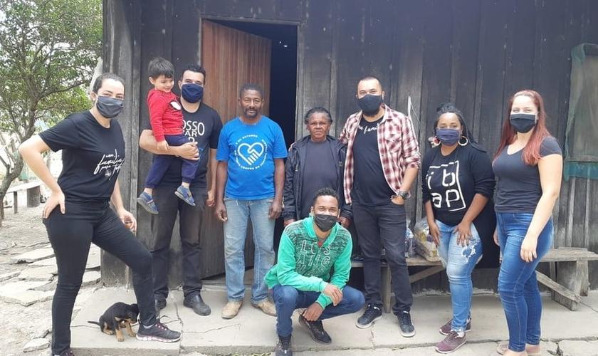 Pastor Samuel Santos (blusa xadrez) e outros voluntários visitam famílias ribeirinhas necessitadas para entregar alimentos e materiais para reconstruir as casas. (Foto: Arquivo Pessoal)