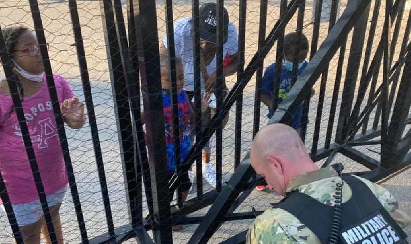 O soldado Dan Otterson (de farda) se ajoelhou, enquanto o garoto de 5 anos orou por ele, do outro lado da cerca. (Foto: Facebook)