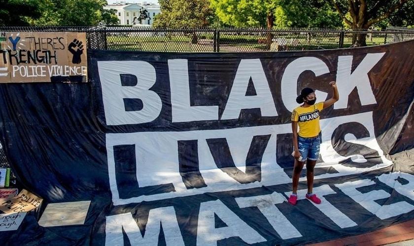 Militante faz posição sinalizando gesto símbolo do Black Lives Matter em protesto nos EUA. (Imagem: Fox News)