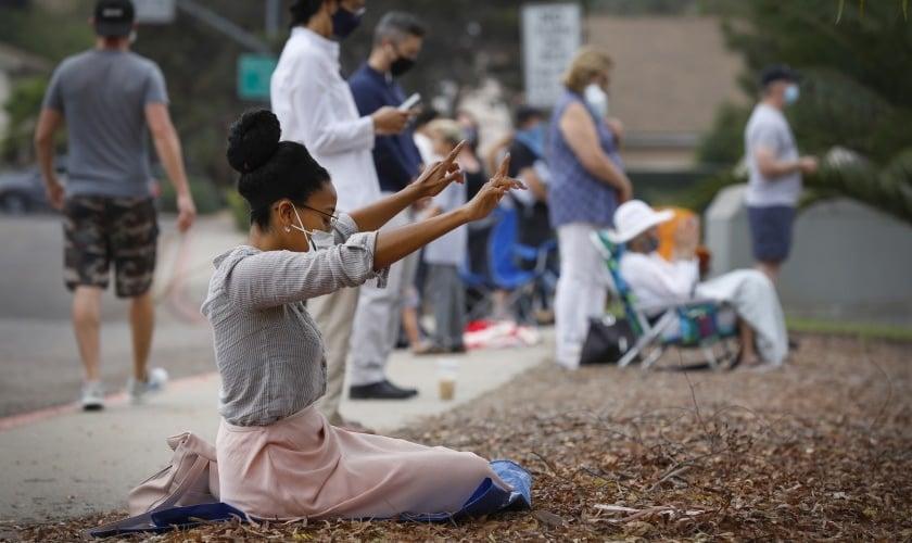 """Mulher ora em frente ao colégio Mt. Carmel durante o evento """"We Pray San Diego"""", na Califórnia. (Foto: Nancee E. Lewis/San Diego Union Tribune)"""