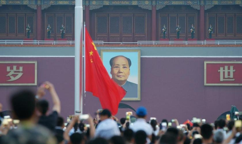 Visitantes acompanham uma cerimônia de hasteamento da bandeira com a imagem de Mao Tsé Tung ao fundo, na praça Praça da Paz Celestial, em Pequim, em julho de 2018. (Foto: CHINA STRINGER NETWORK/REUTERS/Newscom)