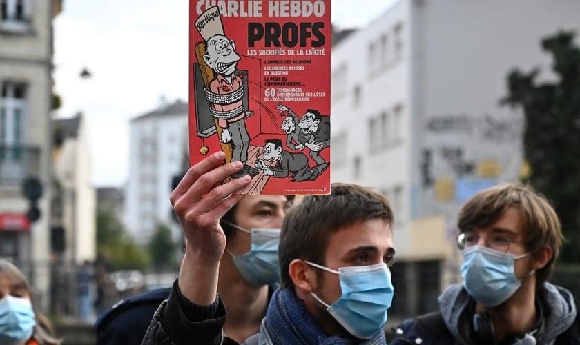 Manifestante segura capa do Charlie Hebdo, um dia após o professor ter sido decapitado na França. (Foto: Damien Meyer/AFP)