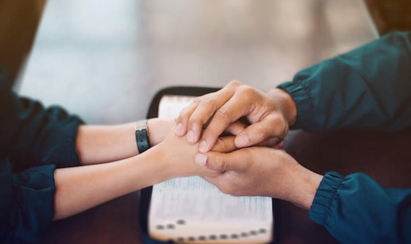 Imagem ilustrativa de casal com as mãos sobre a Bíblia. (Foto: Jantanee/Lightstock)