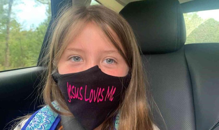 """Lydia Booth foi proibida de usar sua máscara com a inscrição """"Jesus Loves Me"""" (""""Jesus me Ama"""") e agora sua família está processando a escola onde ela cursa a 3ª série. (Foto: Alliance Defending Freedom)"""