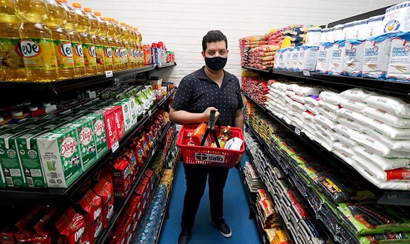 Luander Oliveira, coordenador do Mercado Solidário, em meio às prateleiras com doações. (Foto: Rafaelly Machado)