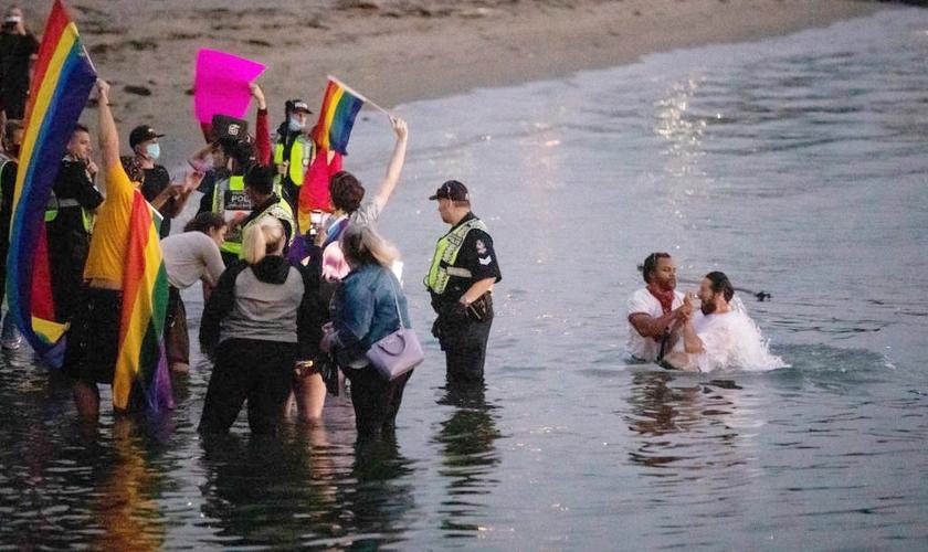 Multidão hostiliza o pregador de rua David Lynn durante batismo na English Bay, em Vancouver, em 31 de agosto de 2020. (Foto: The Canadian Press/Darryl Dyck)