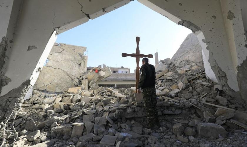 Um membro das forças árabes-curdas da Síria coloca uma cruz nos escombros antes de uma celebração de Natal na Igreja Católica Armênia dos Mártires, no centro da cidade de Raqa, leste da Síria, em 26 de dezembro de 2017. (Foto: DELIL SOULEIMAN / AFP)