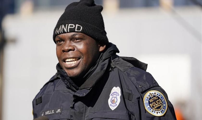 O policial James Wells evacuou pessoas antes de uma explosão no centro de Nashville na manhã de Natal. (Foto: Mark Humphrey/AP)