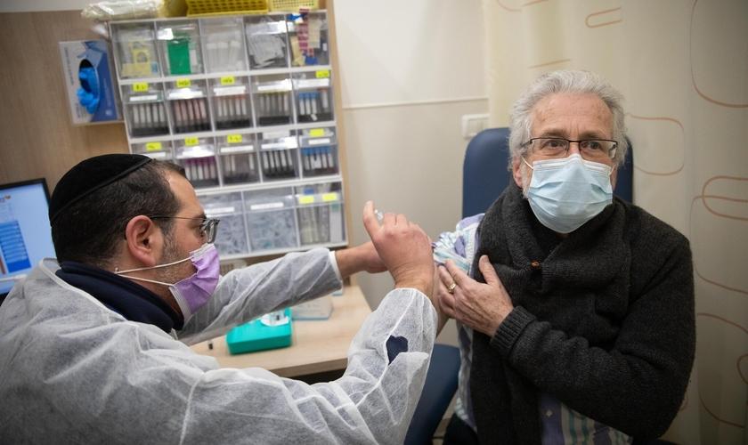 Homem recebe vacina da Covid-19 em posto de vacinação de Jerusalém, em 30 de dezembro de 2020. (Foto: Noam Revkin Fenton/Flash90)