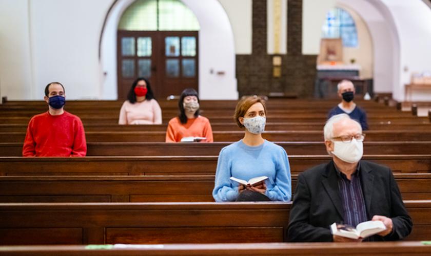 Fiéis em igreja usando máscaras e mantendo distanciamento social. (Foto: Luis Alvarez/Getty Images)