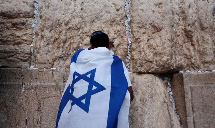 Jovem durante oração no Muro das Lamentações, coberto com a bandeira de Israel. (Foto: Reuters/Darren Whiteside)