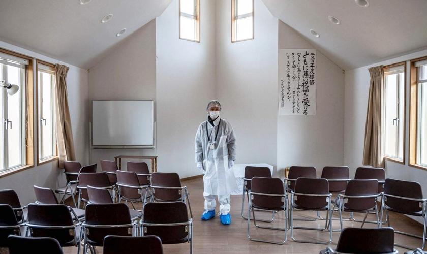 Reverendo Akira Sato usa traje de proteção no templo abandonado da antiga Primeira Igreja Batista Bíblica de Fukushima. (Foto: AFP)