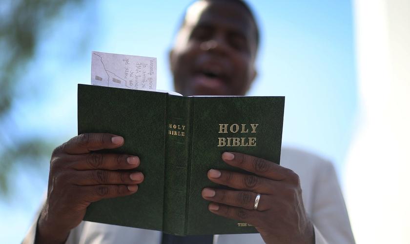 Pastor lê a Bíblia enquanto conduz uma oração, nos EUA. (Foto: Joe Raedle/Getty Images)