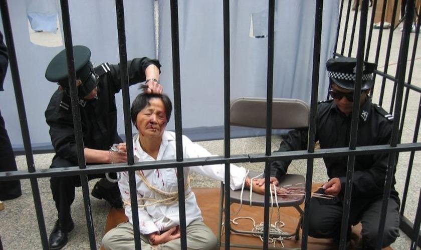 Reconstituição de um praticante do Falun Gong sendo torturado pela polícia em um centro de detenção. (Foto: Minghui.tv)