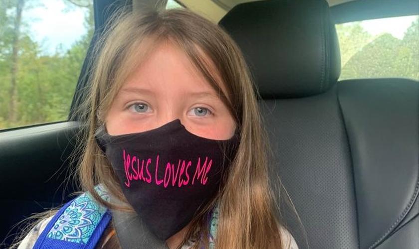 "Lydia Booth foi proibida de usar sua máscara com a frase ""Jesus Loves Me"". (Foto: Alliance Defending Freedom)"