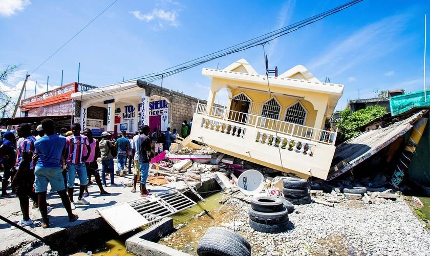 Pessoas do lado de uma casa destruída após um terremoto de magnitude 7,2 em Les Cayes, Haiti. (Foto: Ralph Tedy/Reuters)