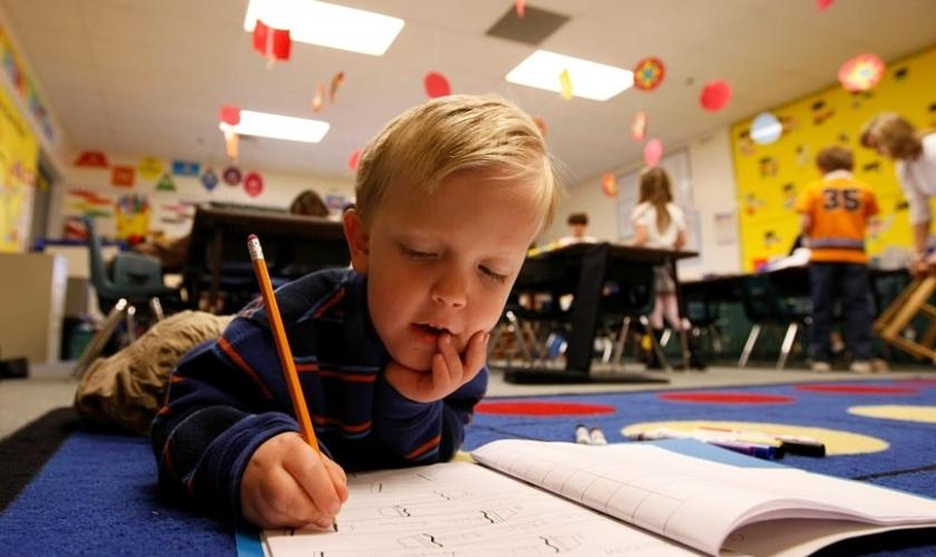 O pequeno Adam Kotzian escolher fazer o seu dever deitado no chão de sua sala de aula, na Eagleview Elementary School, no Estado do Colorado (EUA)