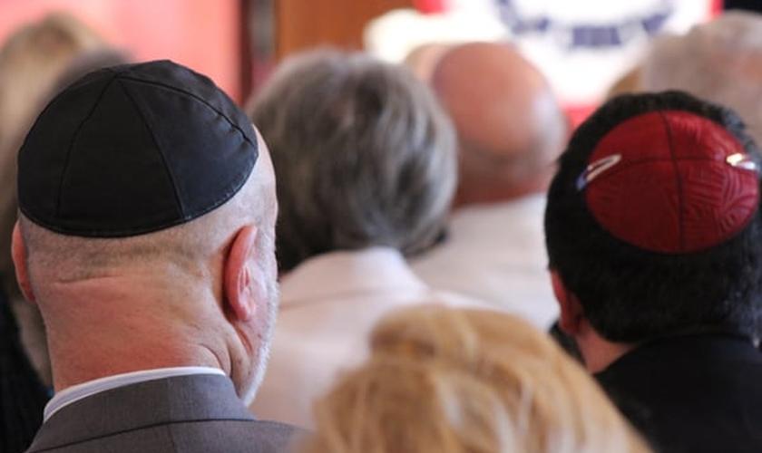 Judeus reunidos em uma sinagoga, utilizando seus quipás sobre a cabeça.
