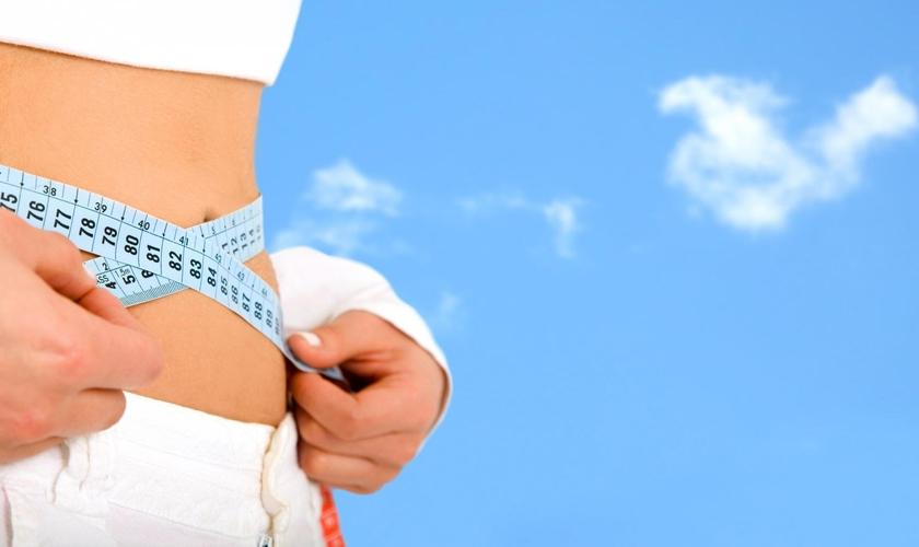 Imagem ilustrativa: mulher medindo a cintura em processo de emagrcimento.