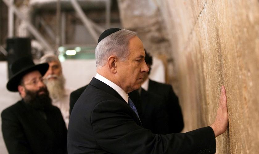 O primeiro-ministro de Israel, Benjamin Netanyahu, toca as pedras do Muro das Lamentações, o lugar do judaísmo mais sagrado para a oração, na Cidade Velha de Jerusalém.
